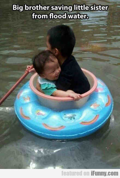Big brother saving little sister from flood water