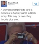 A Woman Attempting To Take A Picture At A Hockey..