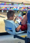 This Kid Is Playing A Bowling Game At A Bowling...